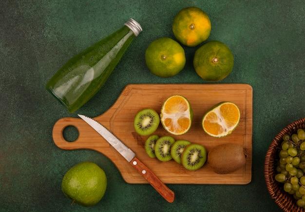 Vista superior de rodajas de kiwi con un cuchillo en la tabla de cortar con mandarinas y una botella de jugo en la pared verde