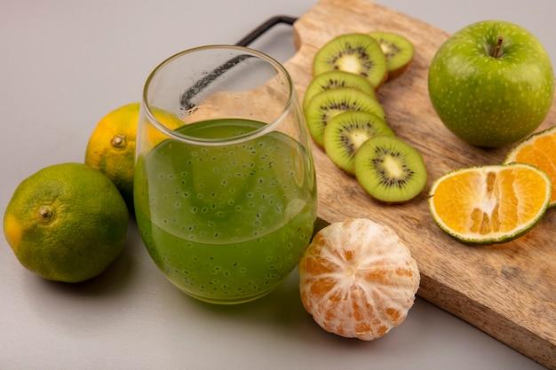 Vista superior de rodajas de kiwi picado saludables con mandarina y manzana en una tabla de cocina de madera con jugo de fruta fresca