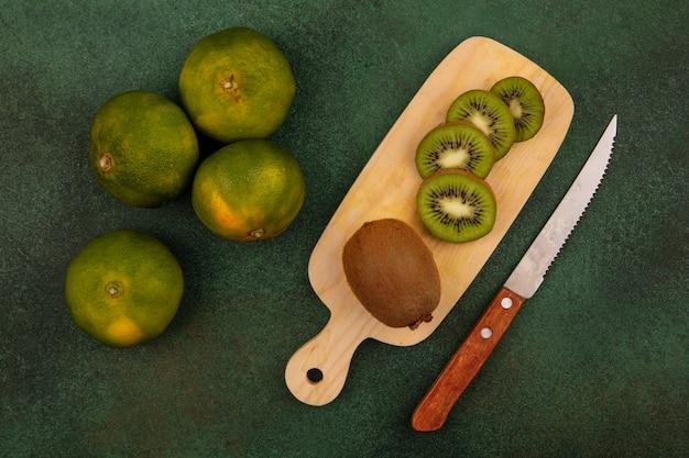 Vista superior de rodajas de kiwi en tabla de cortar con cuchillo y mandarinas en pared verde