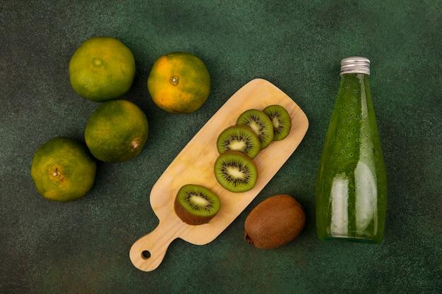 Vista superior de rodajas de kiwi en una tabla de cortar con mandarinas y una botella de jugo en una pared verde