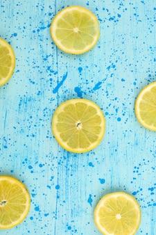 Vista superior en rodajas de limón agrio meloso maduro sobre el fondo azul brillante
