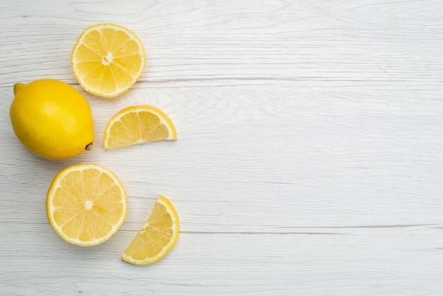 Vista superior en rodajas de limón fresco agrio y jugoso en blanco, jugo tropical de cítricos