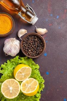 Vista superior de rodajas de limón fresco con ajo y condimentos en la oscuridad