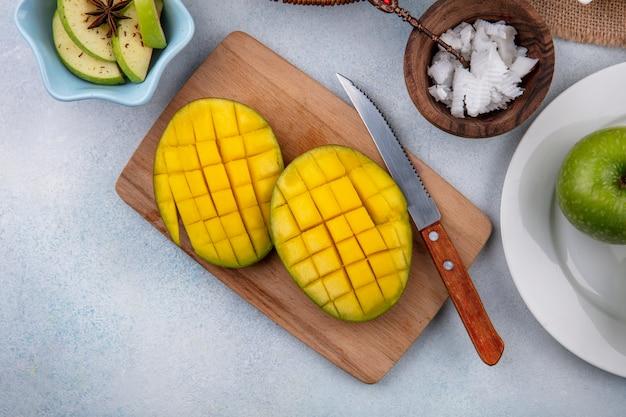 Vista superior de rodajas de mango fresco sobre una tabla de cocina de madera con cuchillo y manzanas picadas en un tazón blanco y pulpas de coco en un tazón de madera sobre una superficie blanca