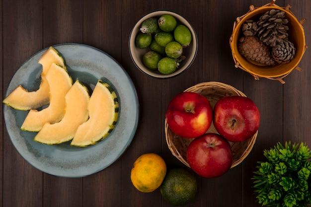 Vista superior de rodajas de melón cantalupo en un plato con feijoas en un recipiente con manzanas en un balde con mandarinas aislado en una pared de madera