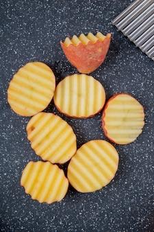 Vista superior de rodajas de patata con volantes en la tabla de cortar como superficie