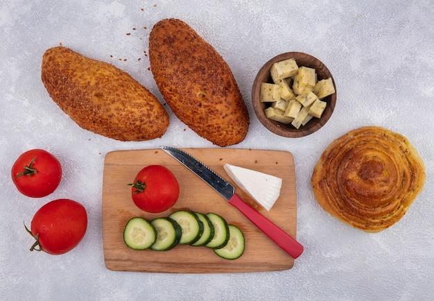 Vista superior de rodajas de pepino con tomate en una tabla de cocina de madera con cuchillo con rodajas picadas de tomates empanadas de queso sobre un fondo blanco.