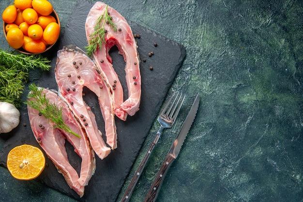 Vista superior de rodajas de pescado fresco con verduras y kumquats sobre fondo oscuro