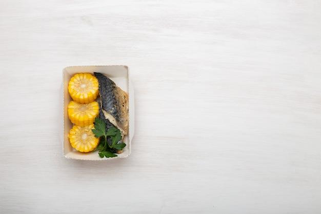 Vista superior de rodajas de pescado y maíz hervido se encuentran en la lonchera junto al calabacín, puerro y maíz. concepto de nutrición saludable, espacio de copia.