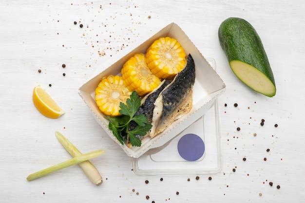Vista superior de rodajas de pescado y maíz hervido se encuentran en la lonchera junto al calabacín, puerro y naranja. concepto de nutrición saludable