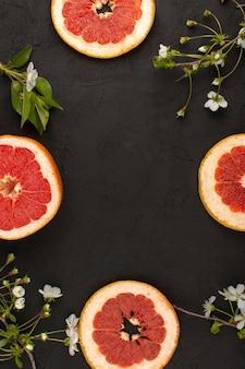 Vista superior en rodajas de pomelo jugoso junto con flor blanca sobre el fondo oscuro