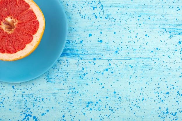 Vista superior rodajas de pomelo jugoso suave en la placa azul y piso azul brillante