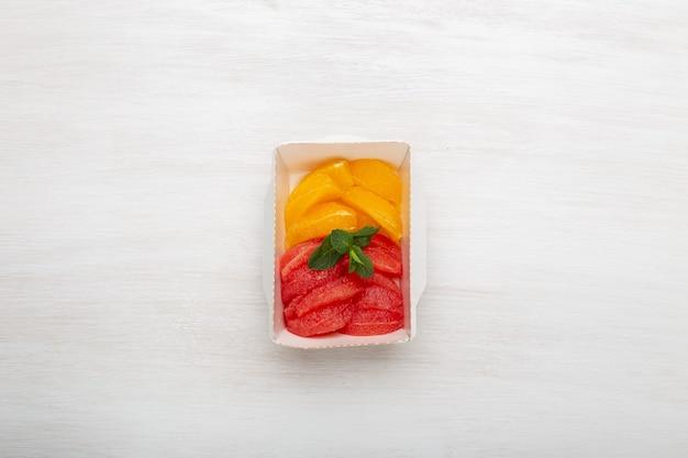Vista superior de rodajas de pomelo y naranja en una lonchera sobre una mesa junto a la mitad de un pomelo y dos naranjas. aperitivo de frutas en el concepto de trabajo, espacio de copia.