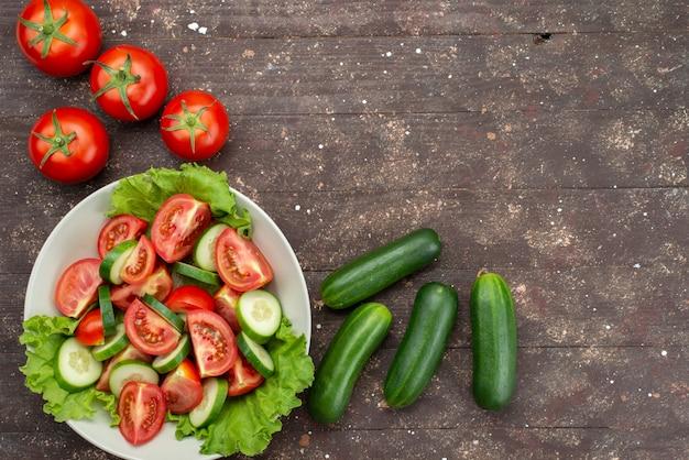 Vista superior rodajas de tomates con pepinos dentro de un plato blanco con ensalada verde junto con verduras frescas en marrón, ensalada de vegetales frescos de alimentos