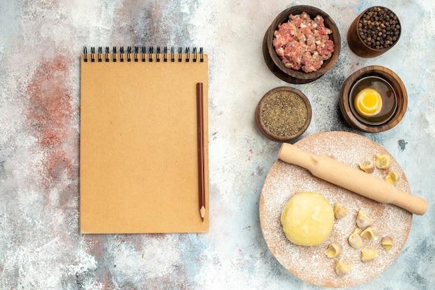 Vista superior rodillo de masa dushbara en tazones de tablero de pastelería de masa con carne, pimienta, yema de huevo, lápiz de cuaderno sobre superficie desnuda