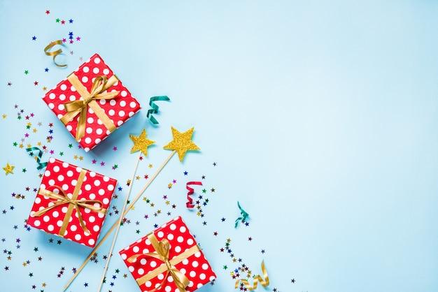 Vista superior de un rojo punteado cajas de regalo, varitas mágicas doradas, confeti de colores y cintas sobre fondo azul. concepto de celebración. copia espacio