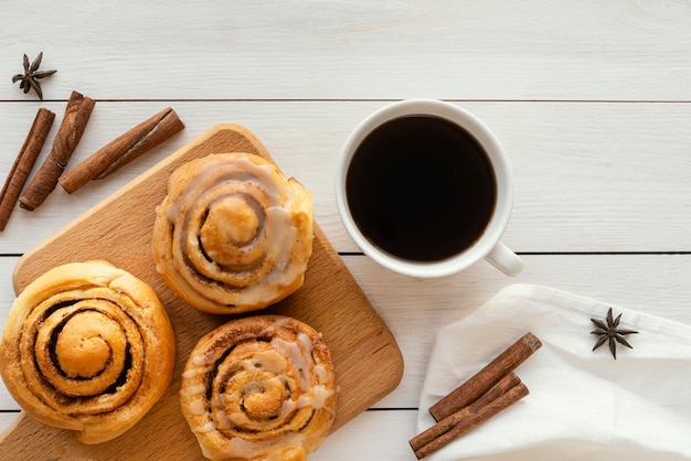 Vista superior del rollo de canela y una taza de café.