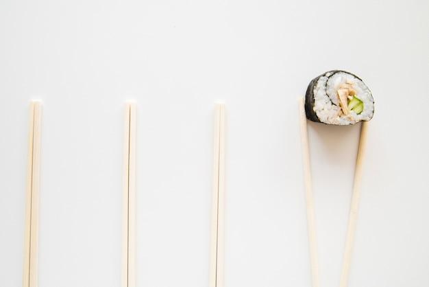 Vista superior del rollo de sushi con palillos