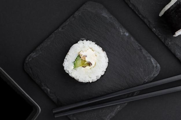 Vista superior del rollo de sushi en pizarra
