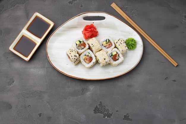 Vista superior del rollo de sushi con sésamo en superficie gris oscuro