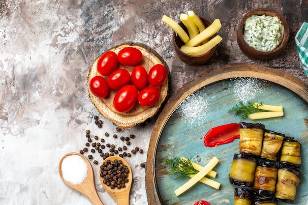Vista superior rollos de berenjena a la parrilla tomates en plato tomates cherry en tablero de madera especias en cucharas de madera toalla de cocina verde en nude