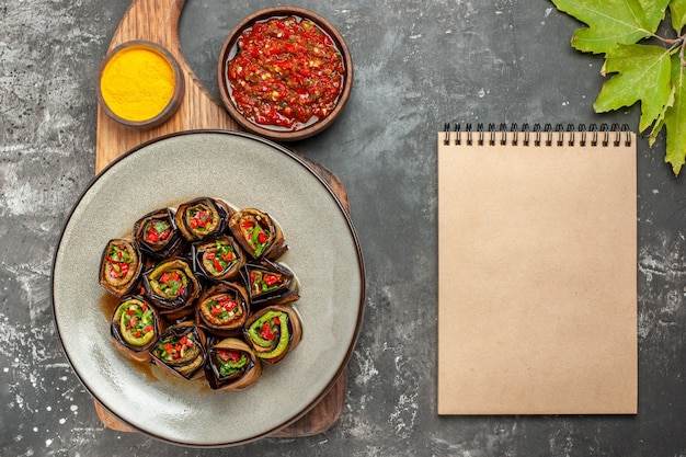 Vista superior rollos de berenjena rellenos en plato ovalado blanco cúrcuma en un tazón sobre tabla de servir de madera con asa adjika un cuaderno sobre fondo gris