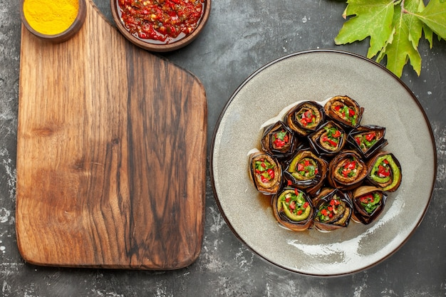 Vista superior rollos de berenjena rellenos en plato ovalado blanco cúrcuma en un tazón sobre tabla de servir de madera con mango adjika sobre fondo gris