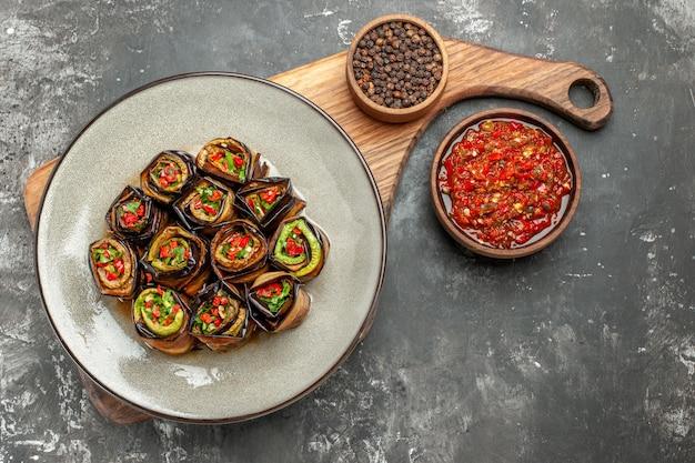 Vista superior rollos de berenjena rellenos en plato ovalado blanco pimienta negra en un tazón sobre tabla de servir de madera con mango adjika sobre fondo gris