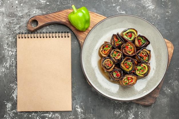 Vista superior de rollos de berenjena rellenos en plato ovalado, un pimiento verde en una tabla de madera con mango, diferentes especias en pequeños gritos, un cuaderno sobre una superficie gris