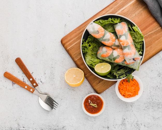 Vista superior de rollos de camarones frescos en un tazón con salsa