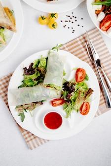 Vista superior de rollos de col con verduras y salsa en la mesajpg