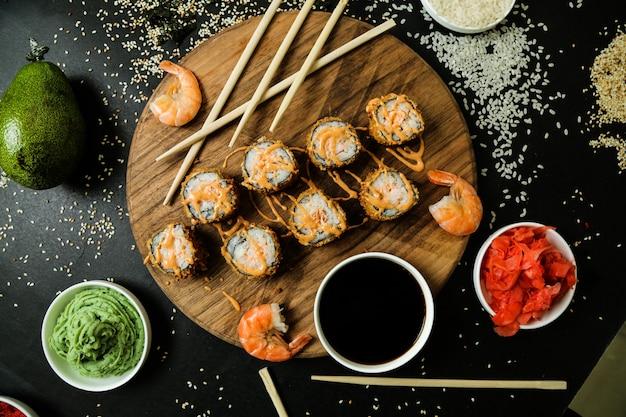 Vista superior rollos fritos en un soporte con salsa y camarones y wasabi de jengibre y salsa de soja