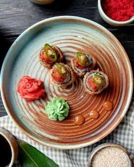 Vista superior de rollos de sushi fritos calientes con wasabi y jengibre en un plato sobre madera