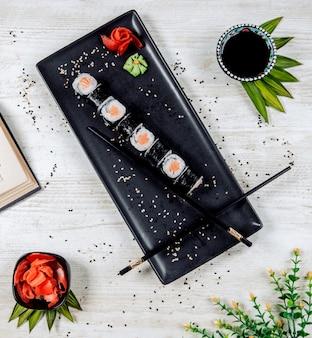 Vista superior de los rollos de sushi nori servidos con jengibre y wasabi
