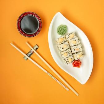 Vista superior de rollos de sushi servidos con salsa de soja, wasabi y jengibre