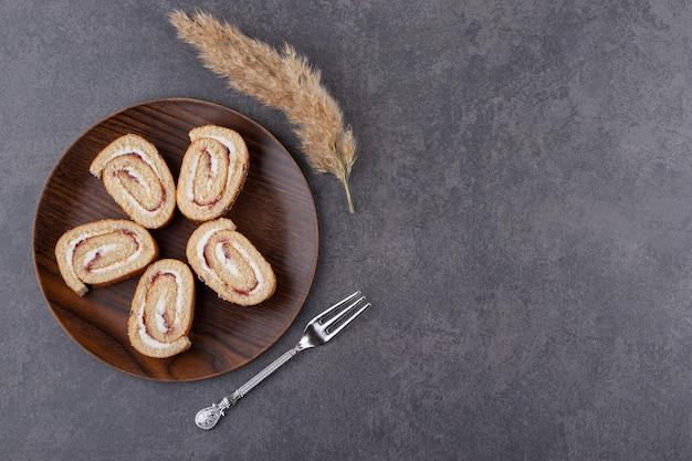 Vista superior de rollos de tarta casera en tablero de madera