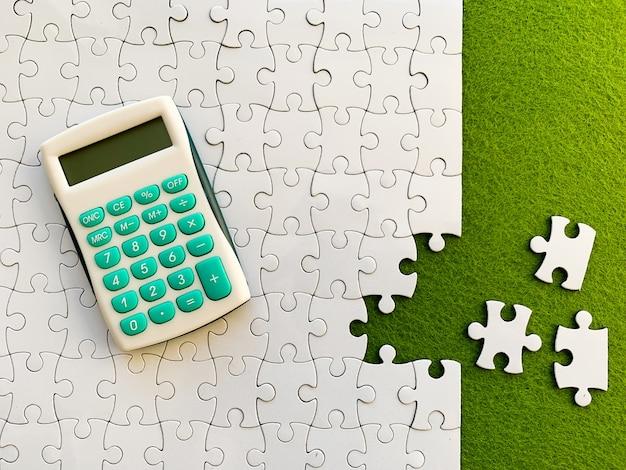 Vista superior, rompecabezas blanco y calculadora en verde