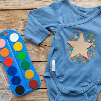 Vista superior de ropa de bebé y acuarela.