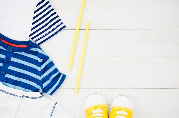 Vista superior de ropa de bebé con fondo de madera