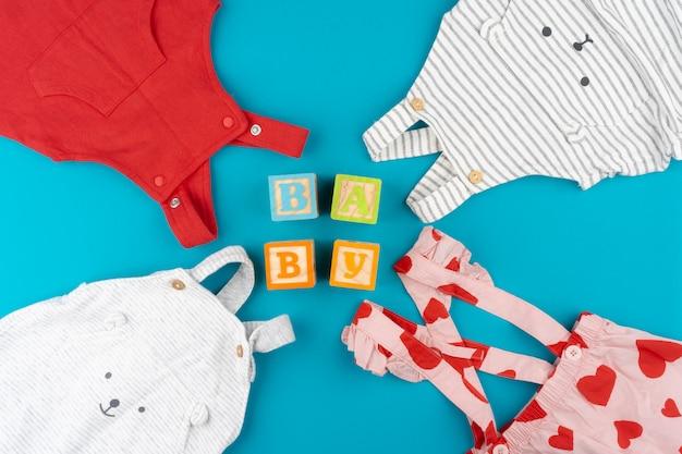 Vista superior de ropa de bebé sobre fondo azul.