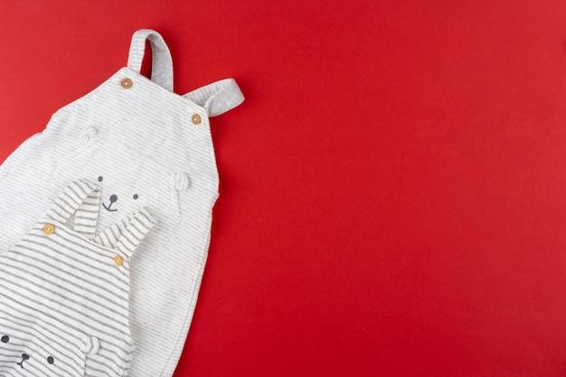 Vista superior de ropa de bebé sobre fondo rojo