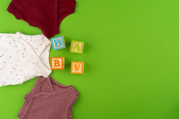 Vista superior de ropa de bebé sobre fondo verde