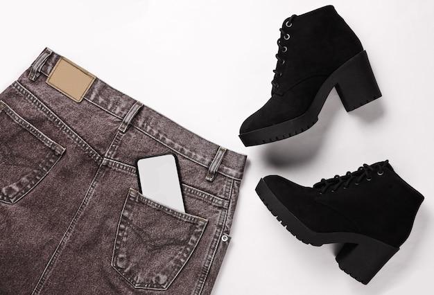 Vista superior de ropa de moda, zapatos sobre un fondo blanco. falda vaquera, botas negras, smartphone en el bolsillo trasero