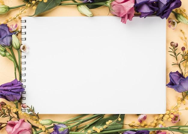 Vista superior de rosas alrededor del cuaderno