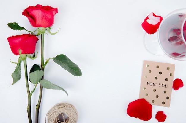 Vista superior de rosas de color rojo con una copa de vino tinto pequeña postal con cuerda sobre fondo blanco con espacio de copia