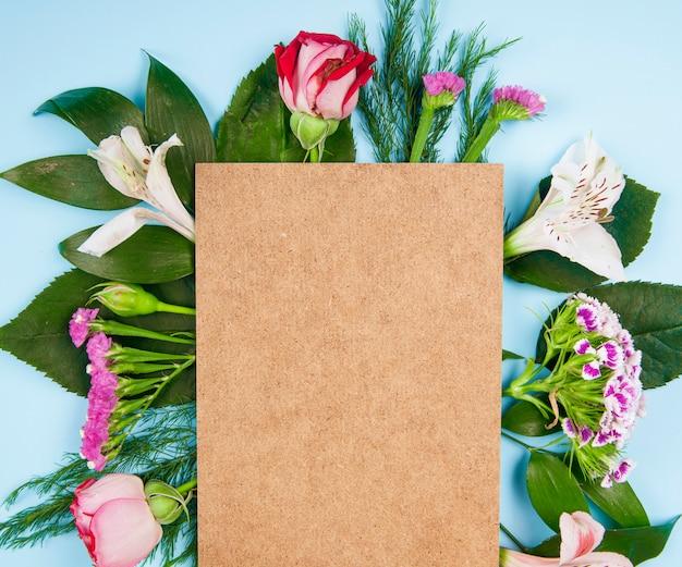 Vista superior de rosas de color rosa y blanco y flores de alstroemeria con clavel turco y statice con una hoja de papel marrón sobre fondo azul.
