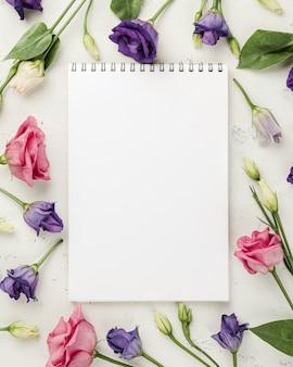 Vista superior rosas coloridas al lado del cuaderno