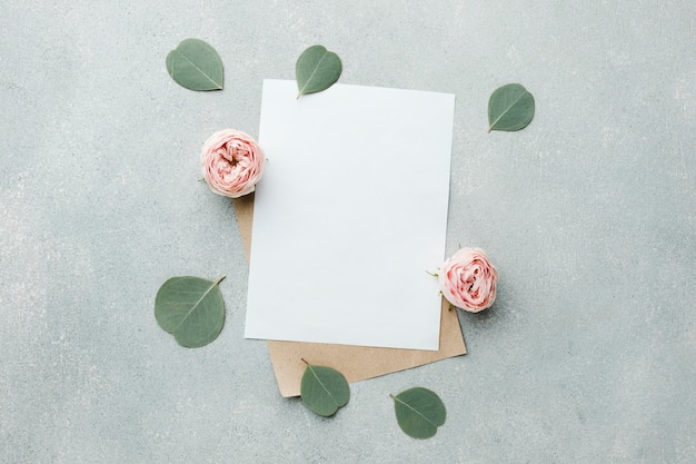 Vista superior de rosas y hojas con papeles en blanco