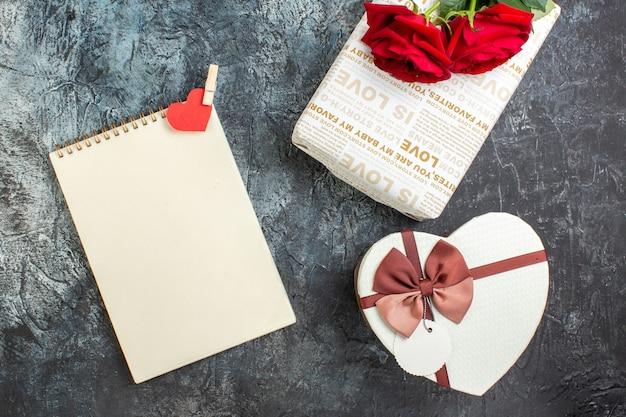 Vista superior de rosas rojas y hermosas cajas de regalo cuaderno de espiral con accesorio de corazón sobre fondo oscuro helado con espacio libre