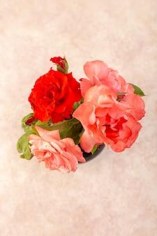 Una vista superior de rosas rojas hermosas flores rosadas dentro de una jarra negra aislada en la mesa y rosa